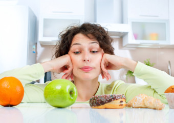 Diet. Dieting concept. Healthy Food. Beautiful Young Woman choosing between Fruits and Sweets. Weight Loss ; Shutterstock ID 160203056; PO: giugno